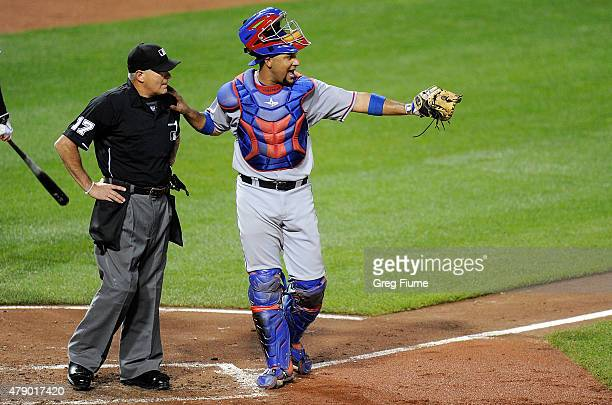 Carlos Corporan of the Texas Rangers holds back home plate umpire John Hirschbeck during the fifth inning against the Baltimore Orioles at Oriole...