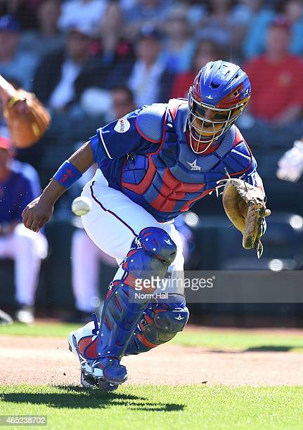 Carlos Corporan of the Texas Rangers makes a play on a bouncing ball behind home plate against the Kansas City Royals on March 4 2015 in Surprise...