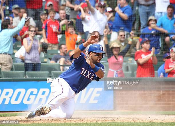 Carlos Corporan of the Texas Rangers slides in safe on a double hit by Leonys Martin in the seventh inning against the Houston Astros at Globe Life...