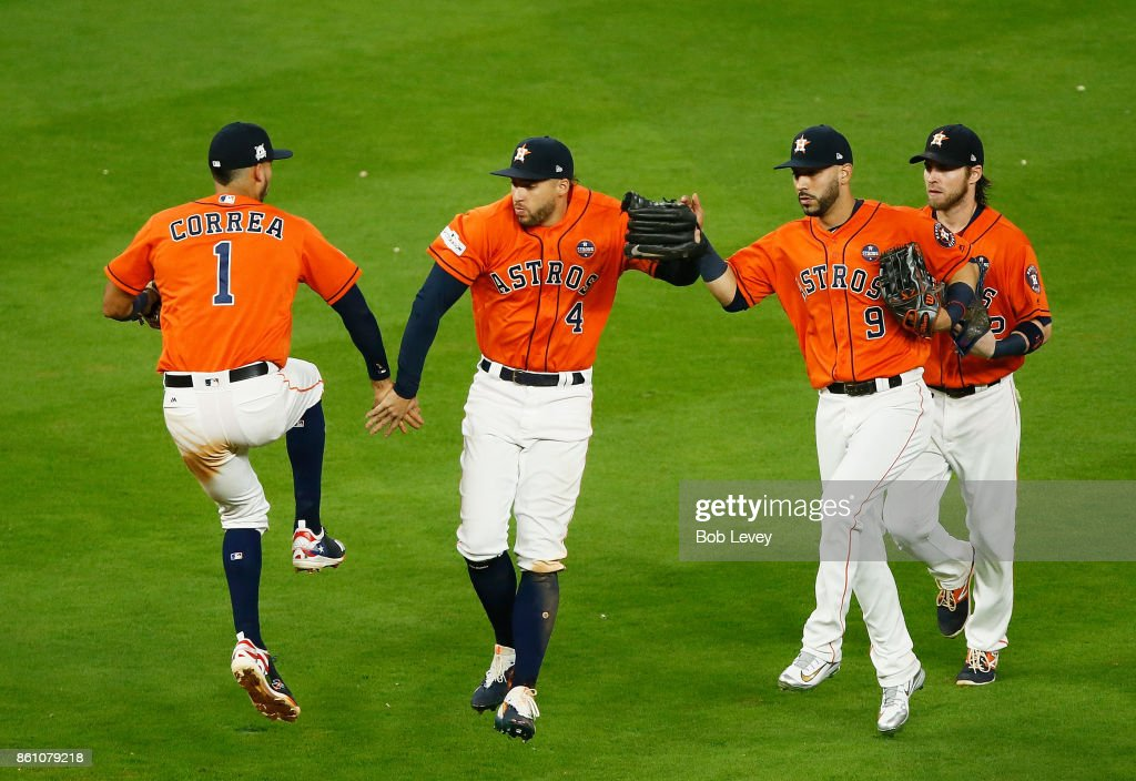 Carlos Correa #1 and George Springer #4 and Marwin Gonzalez #9 of the Houston Astros celebrate their 2 to 1 win over the New York Yankees during game one of the American League Championship Series at Minute Maid Park on October 13, 2017 in Houston, Texas.