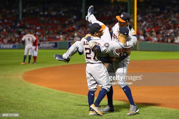 Carlos Correa and Jose Altuve lift Yuli Gurriel of the Houston Astros before a game against the Boston Red Sox at Fenway Park on September 29 2017 in...
