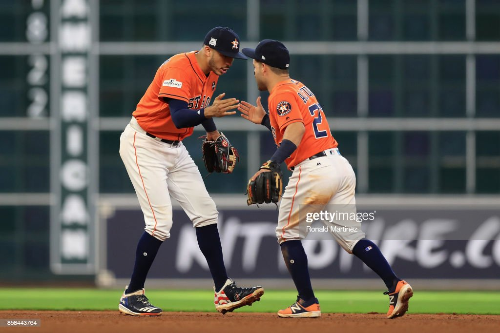 Carlos Correa #1 and Jose Altuve #27 of the Houston Astros celebrate defeating the Boston Red Sox 8-2 in game two of the American League Division Series at Minute Maid Park on October 6, 2017 in Houston, Texas.