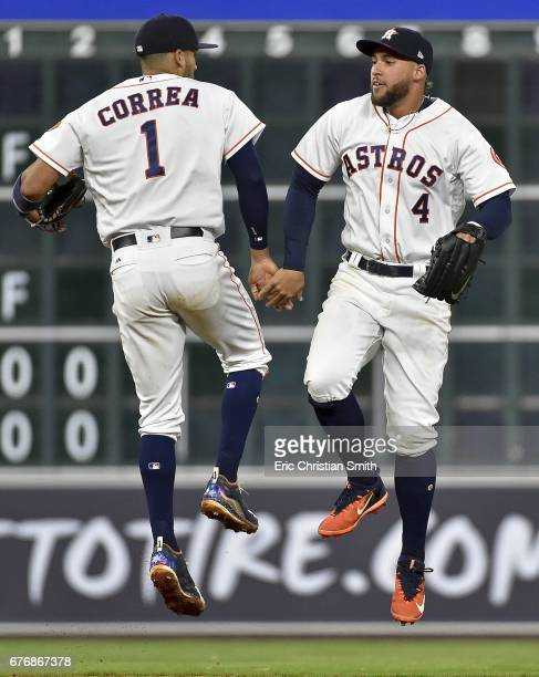 Carlos Correa of the Houston Astros and George Springer celebrate the team's 87 win over the Texas Rangers at Minute Maid Park on May 2 2017 in...