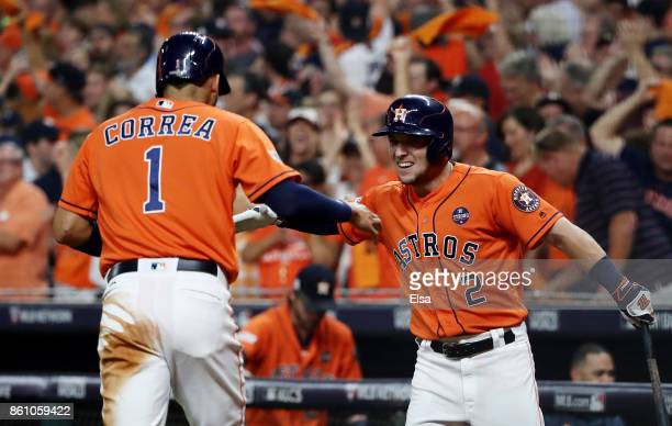 Carlos Correa of the Houston Astros celebrates with Alex Bregman after scoring on a single by Yuli Gurriel in the fourth inning during game one of...