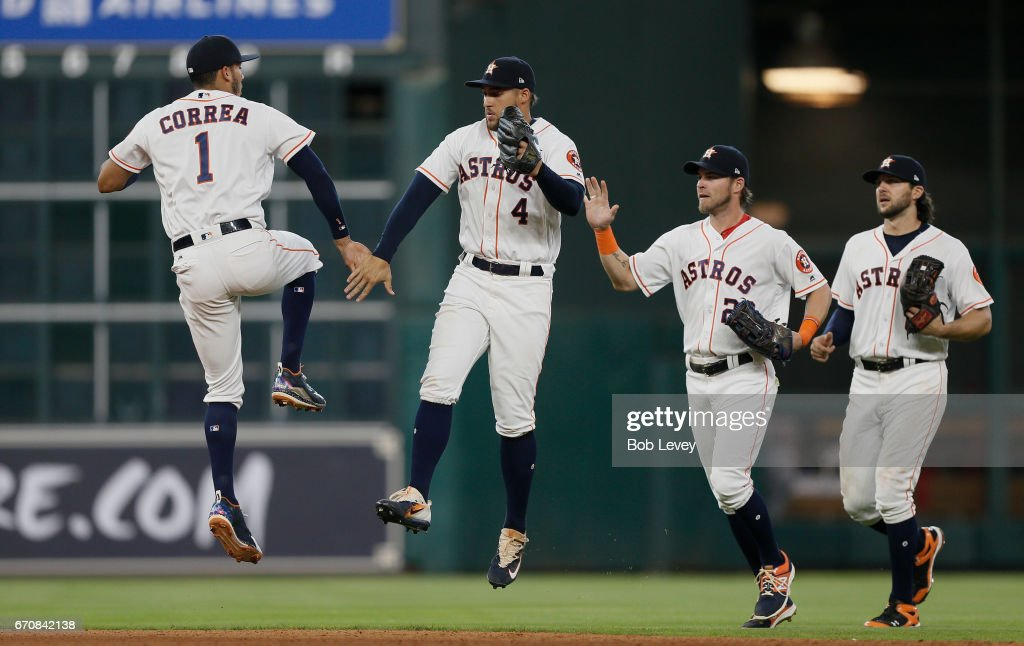 Carlos Correa #1 of the Houston Astros celebrates with George Springer #4 along with Josh Reddick #22 and Jake Marisnick #6 after the final out against the Los Angeles Angels of Anaheim at Minute Maid Park on April 20, 2017 in Houston, Texas.