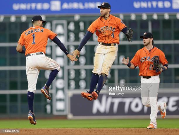 Carlos Correa of the Houston Astros celebrates with George Springer and Josh Reddick after the final out against the Minnesota Twins at Minute Maid...