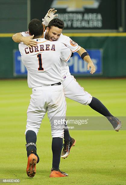 Carlos Correa of the Houston Astros celebrates with his teammate Jose Altuve after Correa drove in the game winning run in the bottom of the 13th...