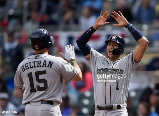 Carlos Correa of the Houston Astros congratulates teammate Carlos Beltran on a threerun home run against the Minnesota Twins during the eighth inning...
