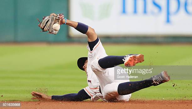 Carlos Correa of the Houston Astros dives for a baseball in the infield during the third inning of their game against the Detroit Tigers at Minute...