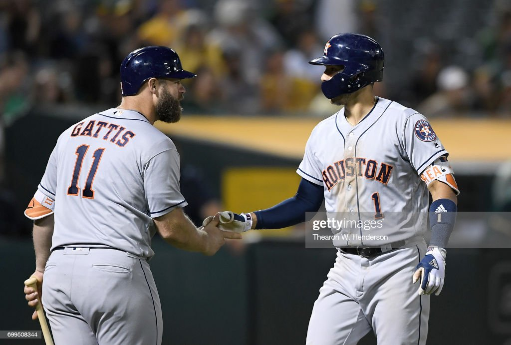 Carlos Correa #1 of the Houston Astros is congratulated by Evan Gattis #11 after Correa hit a solo home run against the Oakland Athletics in the top of the ninth inning at Oakland Alameda Coliseum on June 21, 2017 in Oakland, California. The Astros won the game 5-1.