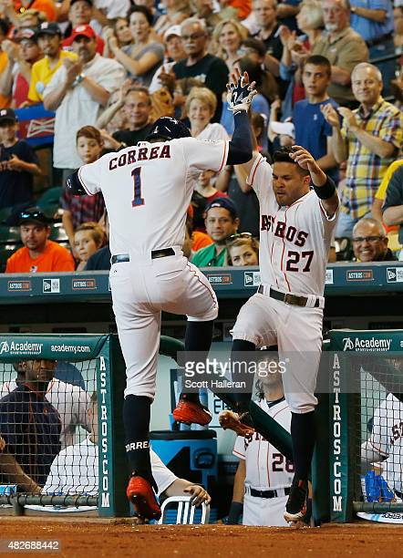 Carlos Correa of the Houston Astros is greeted by teammate Jose Altuve after Correa hit a solo home run in the first inning during their game against...