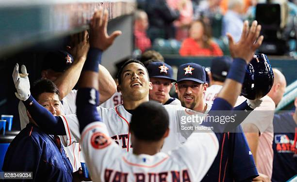 Carlos Correa of the Houston Astros is greeted in the dugout by Luis Valbuena after Correa hit a solo home run in the fourth inning off Casey Fien of...
