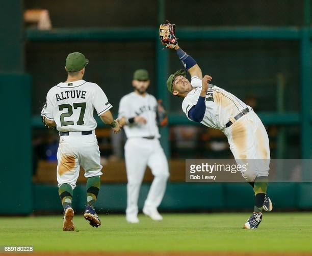 Carlos Correa of the Houston Astros makes a catch on a pop fly to shallow center as Jose Altuve and Marwin Gonzalez look on in the eighth inning...