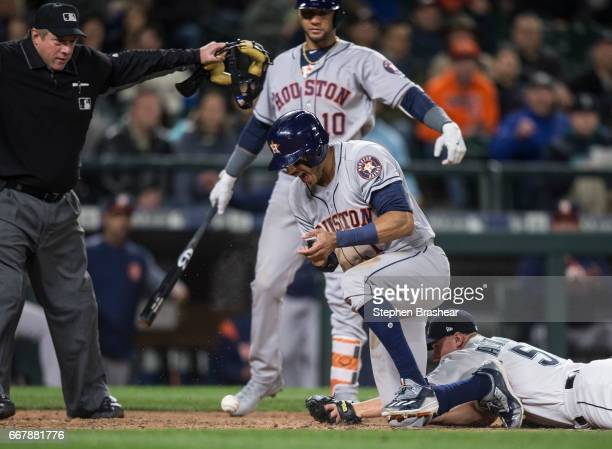 Carlos Correa of the Houston Astros reacts after scoring a run on a while pitch by relief pitcher Dan Altavilla lower right of the Seattle Mariners...