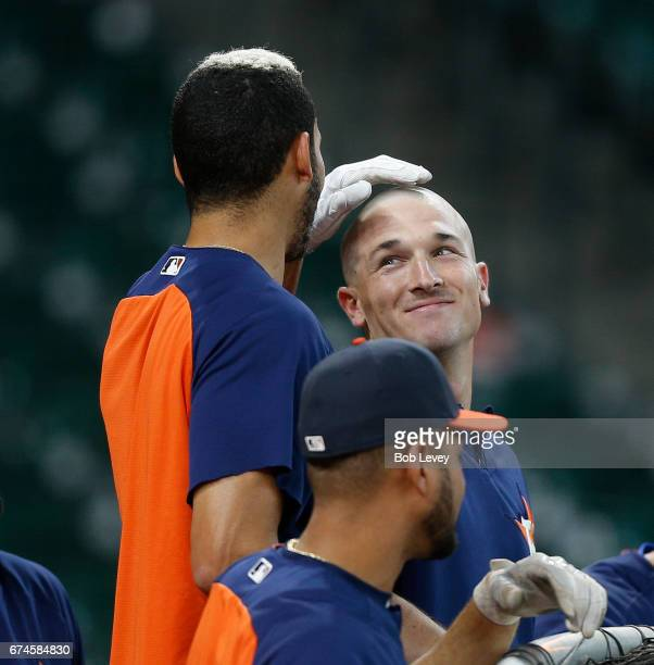 Carlos Correa of the Houston Astros rubs the freshlt shaven head of Alex Bregman during batting practice at Minute Maid Park on April 28 2017 in...