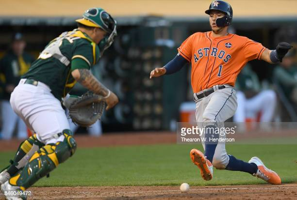 Carlos Correa of the Houston Astros scores as catcher Bruce Maxwell of the Oakland Athletics can't handle the throw in the top of the six inning at...