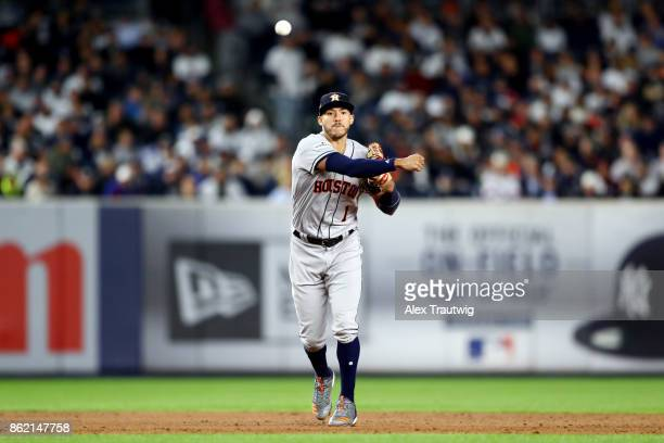 Carlos Correa of the Houston Astros throws to first base for the out during Game 3 of the American League Championship Series against the New York...