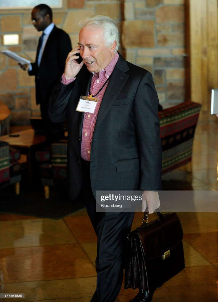 Carlos da Silva Costa, governor of the Bank of Portugal, talks on a mobile phone as he arrives at the Jackson Hole economic symposium, sponsored by the Kansas City Federal Reserve Bank at the Jackson Lake Lodge in Moran, Wyoming, U.S., on Friday, Aug. 23, 2013. The U.S. central banks bond buying is a less potent tool for stimulating growth than policy makers believe, two economists said in a paper released today at a Federal Reserve conference. Photographer: Price Chambers/Bloomberg via Getty Images