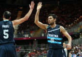 Carlos Delfino of Argentina celebrates a shot with team mate Manu Ginobili in the Men's Basketball Preliminary Round match between France and...