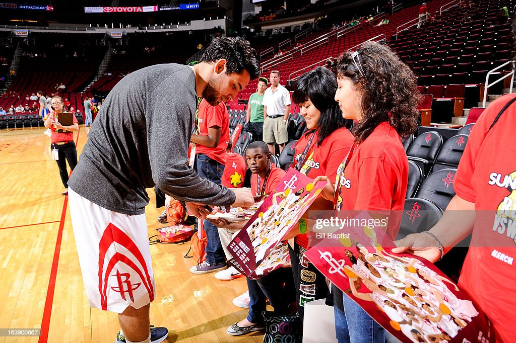 Carlos Delfino #10 of the Houston Rockets autographs posters before a game against the Golden State Warriors on March 17, 2013 at the Toyota Center in Houston, Texas.
