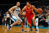 Carlos Delfino of the Houston Rockets drives the ball around Ryan Anderson of the New Orleans Hornets at New Orleans Arena on January 9 2013 in New...
