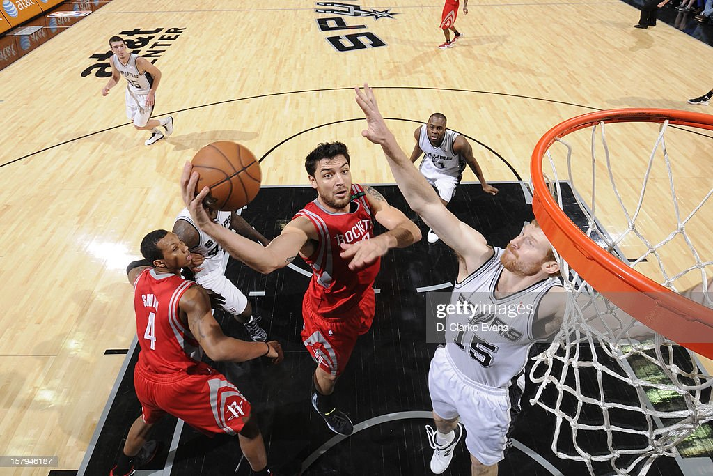 <a gi-track='captionPersonalityLinkClicked' href=/galleries/search?phrase=Carlos+Delfino&family=editorial&specificpeople=206625 ng-click='$event.stopPropagation()'>Carlos Delfino</a> #10 of the Houston Rockets drives to the basket against <a gi-track='captionPersonalityLinkClicked' href=/galleries/search?phrase=Matt+Bonner&family=editorial&specificpeople=203054 ng-click='$event.stopPropagation()'>Matt Bonner</a> #15 of the San Antonio Spurs on December 7, 2012 at the AT&T Center in San Antonio, Texas.