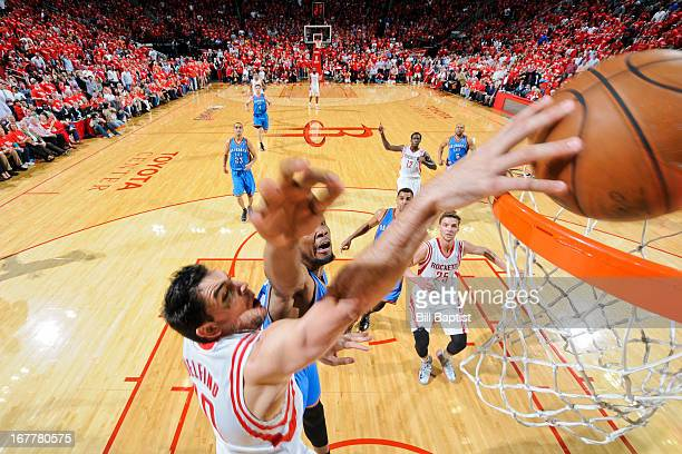 Carlos Delfino of the Houston Rockets dunks the ball against Kevin Durant of the Oklahoma City Thunder in Game Four of the Western Conference...