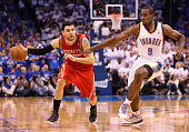 Carlos Delfino of the Houston Rockets handles the ball guarded by Serge Ibaka of the Oklahoma City Thunder during Game Two of the Western Conference...