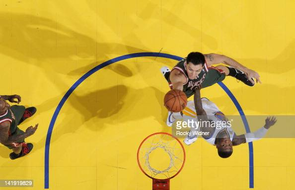 Carlos Delfino of the Milwaukee Bucks puts up a shot over Nate Robinson of the Golden State Warriors on March 16 2012 at Oracle Arena in Oakland...