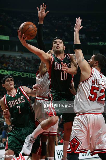 Carlos Delfino of the Milwaukee Bucks shoots a layup against Taj Gibson and Brad Miller of the Chicago Bulls on April 6 2010 at the United Center in...