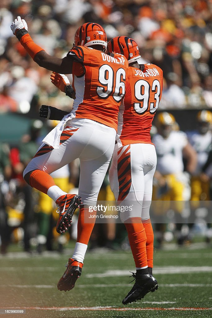 Carlos Dunlap #96 and Michael Johnson #93 of the Cincinnati Bengals celebrate a play during the game against the Green Bay Packers at Paul Brown Stadium on September 22, 2013 in Cincinnati, Ohio.