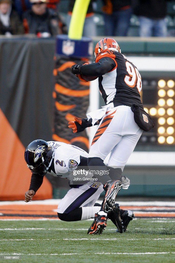 Carlos Dunlap #96 of the Cincinnati Bengals eludes the tackle of Tyrod Taylor #2 of the Baltimore Ravens while returning a second half interception for a touchdown during their game at Paul Brown Stadium on December 30, 2012 in Cincinnati, Ohio. The Bengals defeated the Ravens 23-17.