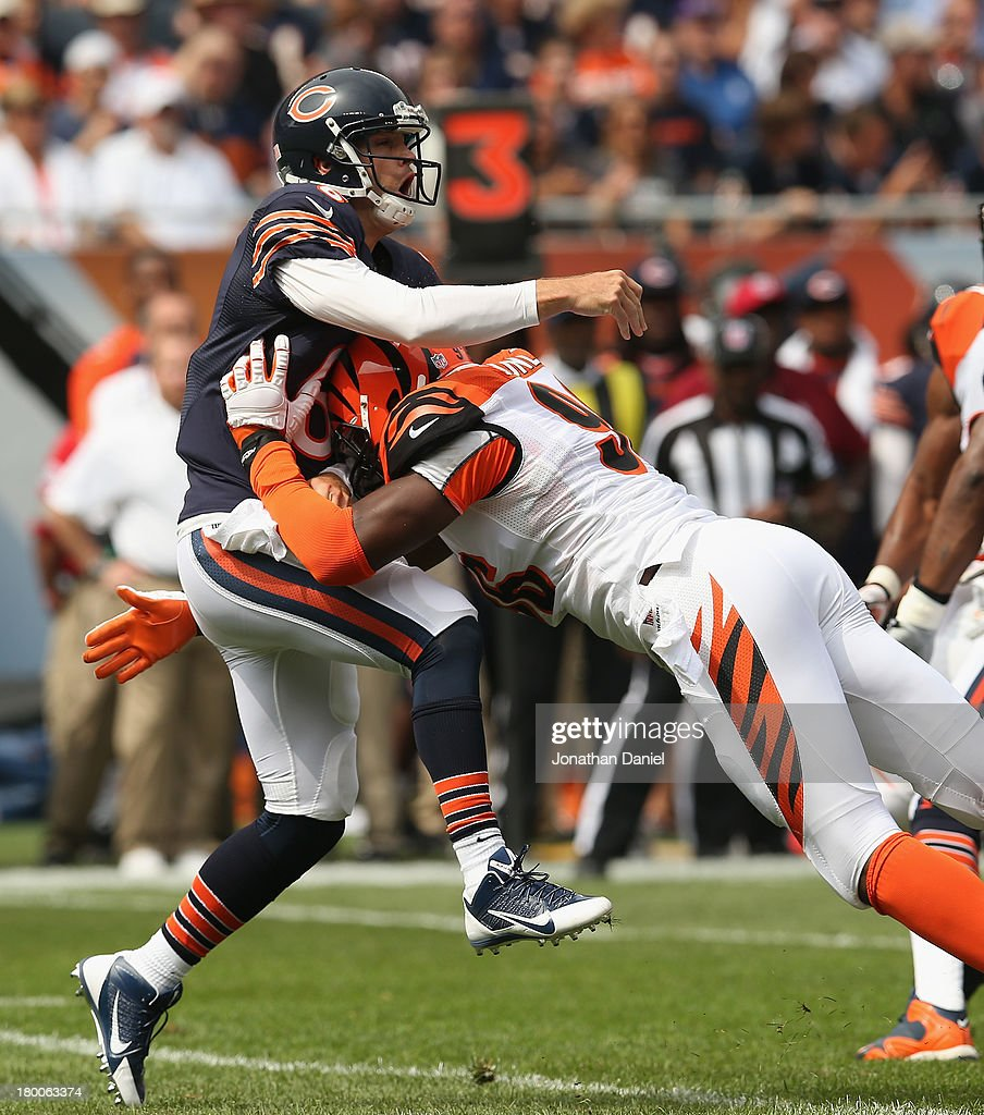 Carlos Dunlap #96 of the Cincinnati Bengals hits Jay Cutler #6 of the Chicago Bears after a pass at Soldier Field on September 8, 2013 in Chicago, Illinois.