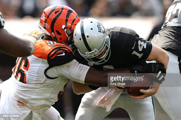 Carlos Dunlap of the Cincinnati Bengals hits Matt McGloin of the Oakland Raiders during the first half of their NFL game at Oco Coliseum on September...