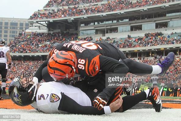 Carlos Dunlap of the Cincinnati Bengals slams Joe Flacco of the Baltimore Ravens to the turf during their game at Paul Brown Stadium on December 29...