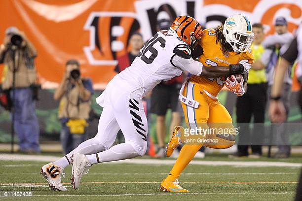 Carlos Dunlap of the Cincinnati Bengals tackles Jay Ajayi of the Miami Dolphins during the second quarter at Paul Brown Stadium on September 29 2016...
