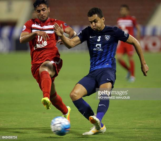 Carlos Eduardo from Saudi's AlHilal fights for the ball against Sadegh Moharrami from Iran's Persepolis during the AFC Champions League qualifying...