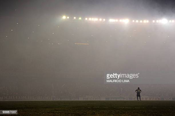 Carlos Espinola of Ecuador's Liga Deportivo de Quito stands on the pitch amid smoke coming from fireworks shot by fans of Brazil's Fluminense at the...