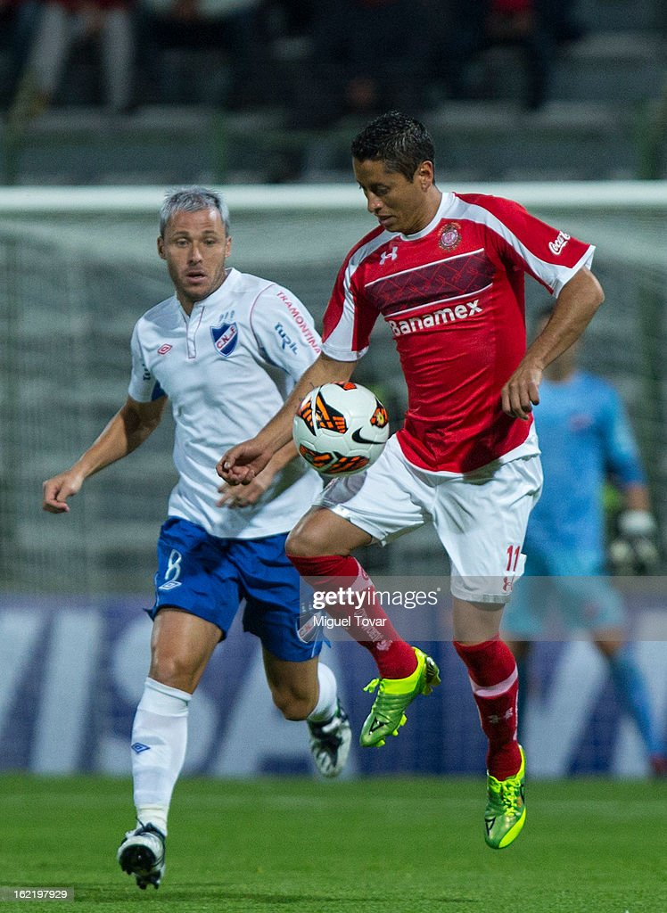 Carlos Esquivel of Toluca (R) fights for the ball with Pablo Alvarez of Nacional de Uruguay (L) during a match for the Bridgestone Libertadores Cup at Nemesio Diez on February 19, 2013 in Toluca, Mexico.