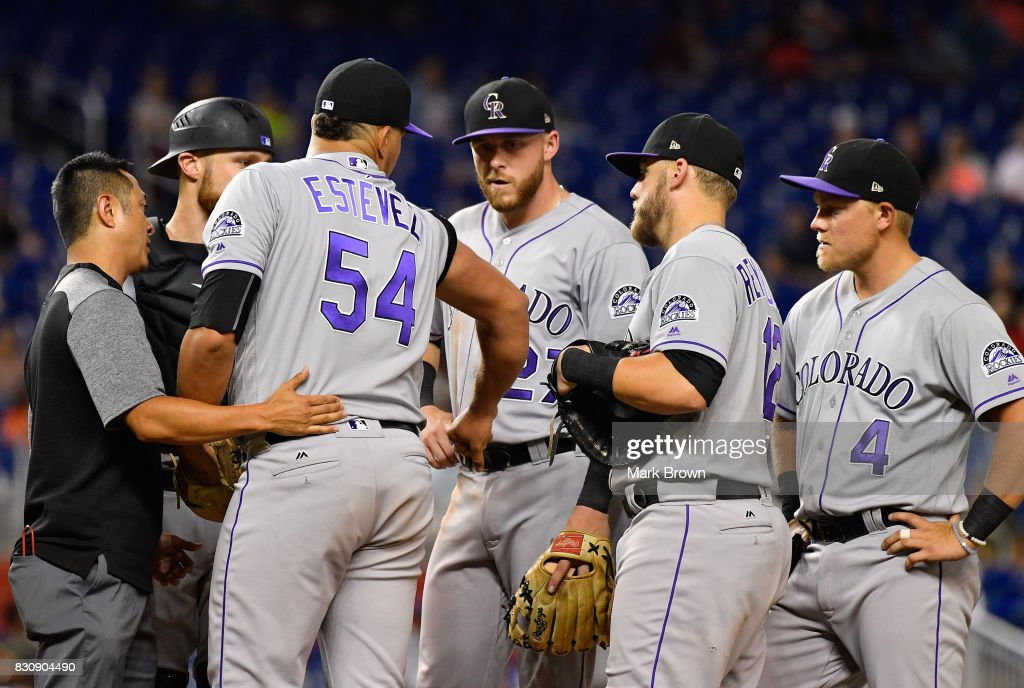 Carlos Estevez #54 of the Colorado Rockies examines his arm after being hit by a line drive in the seventh inning during the game between the Miami Marlins and the Colorado Rockies at Marlins Park on August 12, 2017 in Miami, Florida.