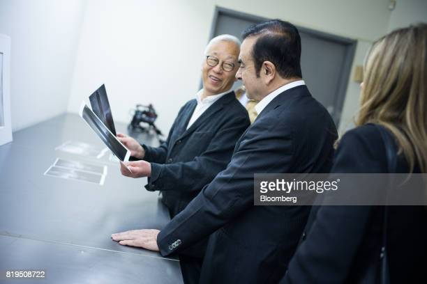 Carlos Ghosn chairman of Renault SAS Nissan Motor Co and Mitsubishi Motors Corp center views prints with Japanese photographerHiroshi Sugimoto at...