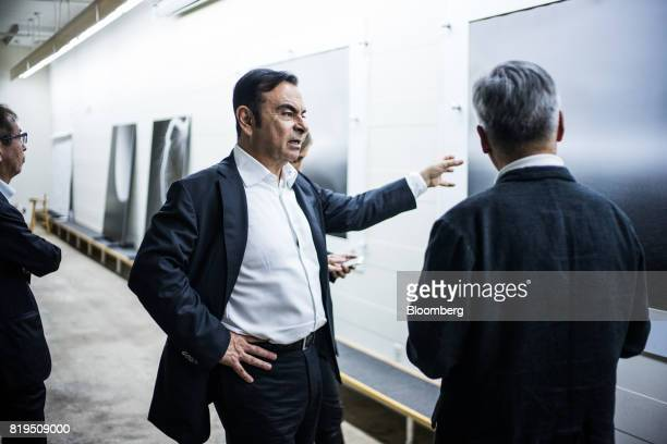 Carlos Ghosn chairman of Renault SAS Nissan Motor Co and Mitsubishi Motors Corp center speaks with Japanese photographerHiroshi Sugimoto right at...