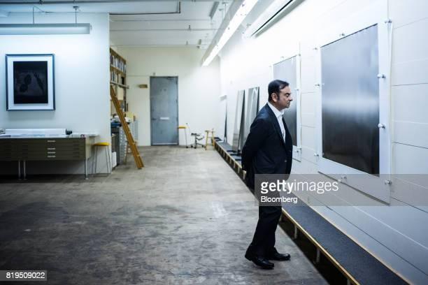Carlos Ghosn chairman of Renault SAS Nissan Motor Co and Mitsubishi Motors Corp views photographs at the studio of Japanese photographerHiroshi...