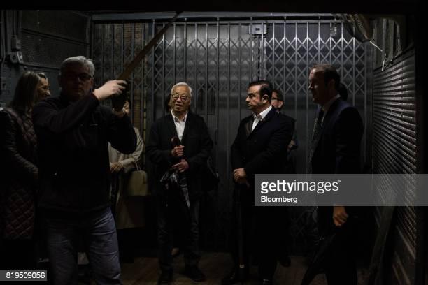 Carlos Ghosn chairman of Renault SAS Nissan Motor Co and Mitsubishi Motors Corp center right and Japanese photographerHiroshi Sugimoto center left...
