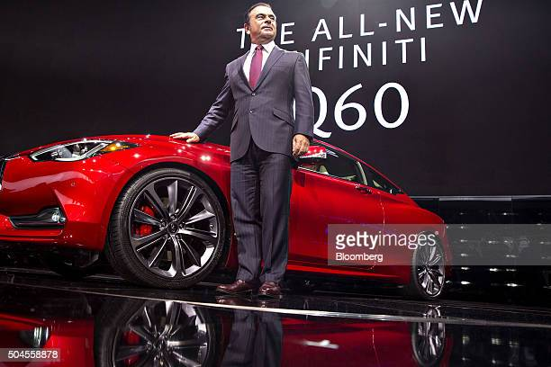 Carlos Ghosn chief executive officer of Nissan Motor Co and Renault SA stands for a photograph next to an Infinity Q60 sedan vehicle at the 2016...