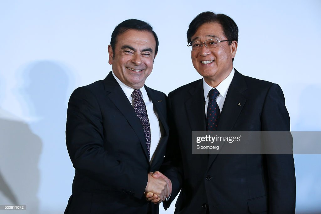 Carlos Ghosn chief executive officer of Nissan Motor Co left shakes hands with Osamu Masuko chairman and chief executive officer of Mitsubishi Motors...