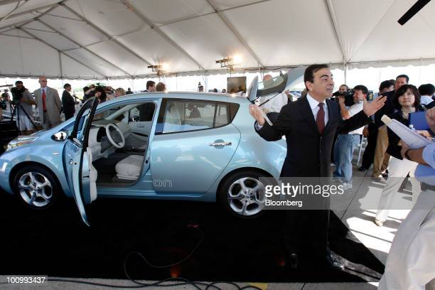 Carlos Ghosn chief executive officer of Nissan Motor Co stands in front of a LEAF electric car as he speaks to the media during the groundbreaking...