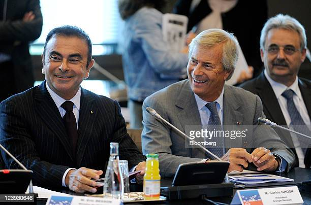 Carlos Ghosn chief executive officer of Renault SA left sits with Vincent Bollore cochief executive officer of Bollore SA center during a news...