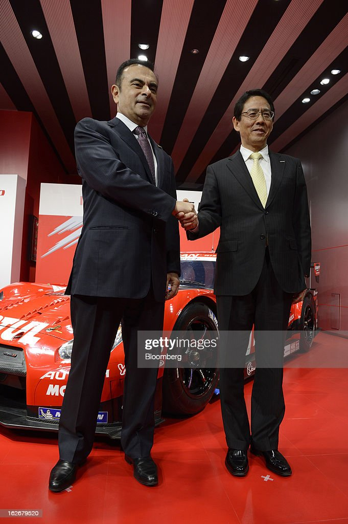 Carlos Ghosn, president and chief executive officer of Nissan Motor Co., left, and Shoichi Miyatani, president of Nissan Motorsports International Co., shake hands as they pose during a photo session at the opening of the Nismo global headquarters and development center in Yokohama City, Japan, on Tuesday, Feb. 26, 2013. Ghosn, who has called 100 yen to the dollar the 'neutral' value for the Japanese currency, said the yen should weaken further. Photographer: Akio Kon/Bloomberg via Getty Images
