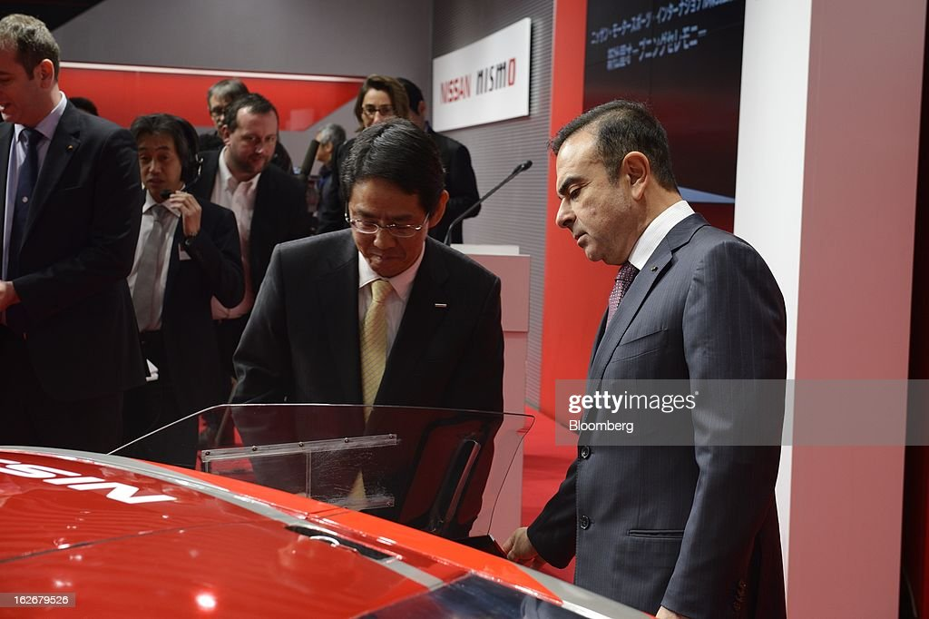 Carlos Ghosn, president and chief executive officer of Nissan Motor Co., right, and Shoichi Miyatani, president of Nissan Motorsports International Co., look at a GT-R Nismo vehicle during a photo session at the opening of the Nismo global headquarters and development center in Yokohama City, Japan, on Tuesday, Feb. 26, 2013. Ghosn, who has called 100 yen to the dollar the 'neutral' value for the Japanese currency, said the yen should weaken further. Photographer: Akio Kon/Bloomberg via Getty Images